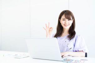 パソコンの前でOKサインをする女性のイメージ