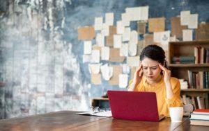 パソコンの前で悩む女性のイメージ